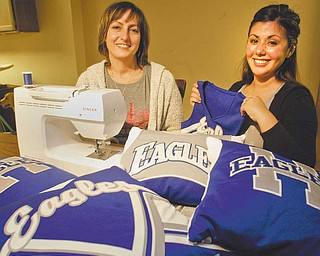 Sharon Sikora, left, mother of Alyssa Sikora, a Hubbard High School cheerleader, and Stephanie Barca, Hubbard head cheerleading coach, show off pillows fashioned from old cheerleading uniforms. Barca said she got the idea from a similar project done years ago. Sikora is using her sewing skills to make the pillows that are being sold as a fundraiser.