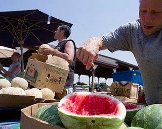 Geoffrey Hauschild|The Vindicator.7.7.2010.OVTC Intern Greg Todd cuts samples of watermelon for patrons as part of a work crew selling produce for Abraham King Produce at the Four Seasons Flea Market along 422 east of Youngstown.