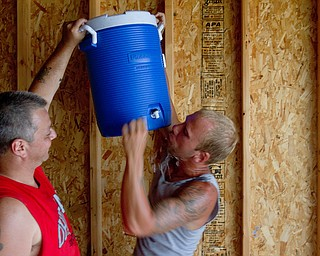 Geoffrey Hauschild|The Vindicator.7.26.2010.OVTC resident John Anderson holds up a cooler as intern Greg Todd takes a drink in Pastor Bob Pavlich's garage while working as part of a crew at nearby Arlington Heights.
