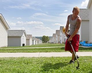 Geoffrey Hauschild|The Vindicator.7.26.2010.OVTC intern Greg Todd leads a work crew in landscaping around the neighborhood of Arlington Heights.