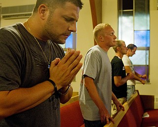 Geoffrey Hauschild|The Vindcator.8.4.2010.OVTC Director of Operations Bob Pavlich prays alongside residents Anthony Sanders and Austin Henderson during the group's Wednesday night weekly church service at Youngstown Christian Assembly.