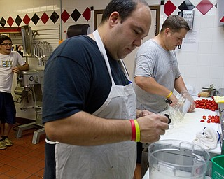 Geoffrey Hauschild|The Vindicator.8.5.2010.OVTC residents Michael Pinkerman, Steve Petracci and Brian Druschel work to complete food for an upcoming catering event while working in the Hope kitchen at OVTC.