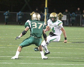 FOOTBALL - (4) Paul Kempe looks for running room as (37) Mark Murphy tries to make the play during their game Thursday night in Akron. - Special to The Vindicator/Nick Mays