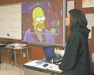 """At left, ninth-grade teacher Rochelle Morelli makes comments to her class during a video clip from an episode of """"The Simpsons,"""" which featured a reading of Edgar Allan Poe's """"The Raven."""" Morelli's students used high-tech learning tools to teach the fourth-graders about Edgar Allan Poe and his classic poem. Morelli's class is studying Gothic literature."""