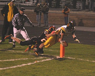 FOOTBALL - (3) Adam Coppock reaches into the end zone as (27) Kaleb Baker makes the tackle Friday night in Mineral Ridge. - Special to The Vindicator/Nick Mays