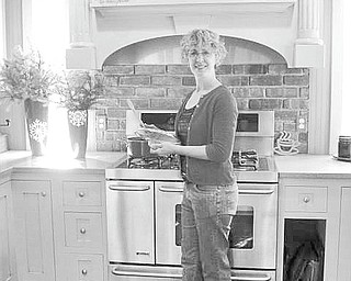 Susan Bissell of Columbiana stands in the enchanting kitchen of her three-story Victorian home, which she and her husband have transformed into a quaint, warm bed and breakfast. The house is one of several that will be on display for the Norman Rockwell Christmas-themed house tour sponsored by the Columbiana Women's Club on Nov. 19 and 20.