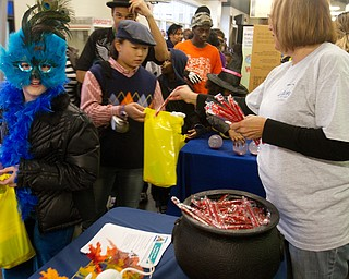 Geoffrey Hauschild The Vindicator.Boardman residents, Haley Nick, 10, dresses as a Peacock, while Jacinta Pikunas, 11, sports a golfers wardrobe while receiving candy from Elaine Vrancich, who manned a booth for Unison By United Health Care at the Covelli Centre on Saturday evening.