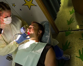 Geoffrey Hauschild|The Vindicator.6.7.2010. Josh Pasture receives a free teeth cleaning from dental hygenist Christy Zedaker of Poland, on board the Mobile Dental Van, a traveling dental service operated by Humility of Mary Health Partners, during one of its regular visits to OVTC. The van most commonly treats Youngstown and Warren city school students, however, residents' appointments are covered through the Health Care Assurance Program.