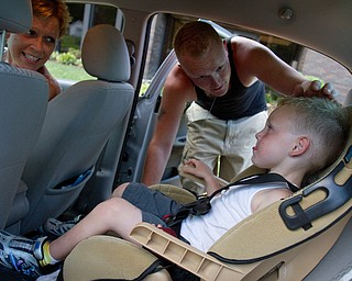 Geoffrey Hauschild|The Vindicator.7.24.2010.OVTC resident Anthony Sanders buckles up his son, Michael, as his mother smiles following a Saturday pass allowing Sanders to leave the center.