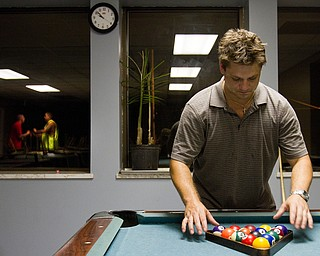 Geoffrey Hauschild|The Vindicator                           .8.6.2010.Michael Malott racks balls for a game of pool, during his free time at Ohio Valley Teen Challenge while the window reflects residents playfully wrestling in the background.