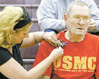 William D LEwis The Vindicator  Jennifer Sehon-Deans pins a corsage on her father James Sehon of Liberty during a Veterans Day program at Liberty HS Thursday. Veterans from Liberty were honored. Sehon served in hte MArines.