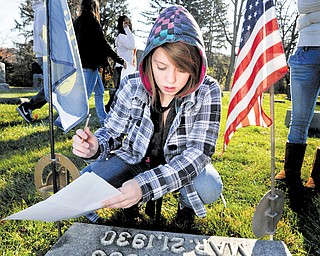 In this Nov. 11, 2010 photo, State College Area High School student Melody Ireland looks at a tombstone at Spring Creek Presbyterian Cemetery in State College, Pa.  Her class was gathering names of veterans to do further research to try and find the soldiers stories. (AP Photo/Centre Daily Times (Knight Ridder), Nabil K. Mark)  MAGS OUT, NO SALES