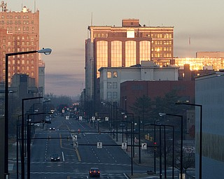 The sunrise reflects off buildings from the East side of Youngstown on Friday morning. (Geoffrey Hauschild | The Vindicator)