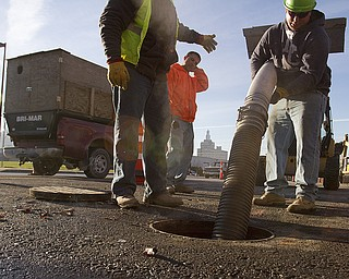 Workers with Marucci and Gaffney Excavating of Youngstown, Dave Mill of Brookfield, Din DiFabio of New Middletown and John Fedoruk of Austintown, remove a sump pump while completing sanitary and road work along Fifth Avenue in Youngstown. (Geoffrey Hauschild | The Vindicator)