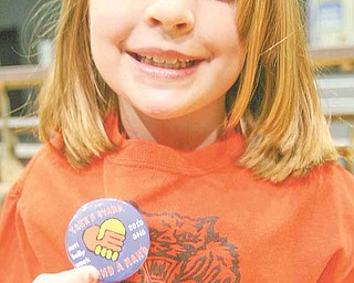 Anti Bully assembly at Struthers Middle School - Mariah Mas  5th grader shows off the buttons each student received from the catholc school to share against bullying .