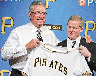 Pittsburgh Pirates new manager Clint Hurdle, left, is presented a Pirates jersey by Pirates general manager Neil Huntington after being introduced as the 39th manager in the history of the Pittsburgh Pirates, Monday, Nov. 15, 2010. (AP Photo/Gene J. Puskar)
