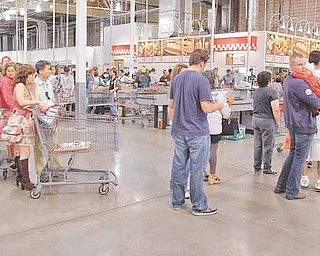In this Nov. 6, 2010 photo, shoppers wait in line at Costco in Mountain View, Calif. The Labor Department said Tuesday, Nov. 16, that the Producer Price Index rose 0.4 percent last month, the same increase as September and August. (AP Photo/Paul Sakuma)