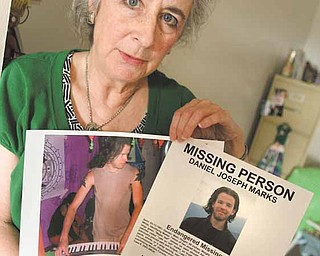 """Patricia """"Pat"""" Marks of Girard holds a photograph and missing-person flier of her son, Daniel Joseph Marks, who disappeared Nov. 10, 2005, on Kauai, Hawaii."""