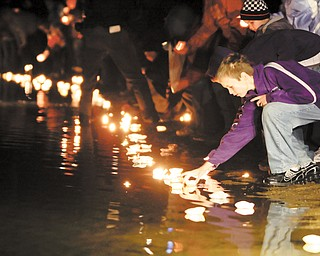 Local residents place candles in the lake during a vigil for the three missing people who were found dead, Thursday, Nov. 18, 2010, in Howard, Ohio.