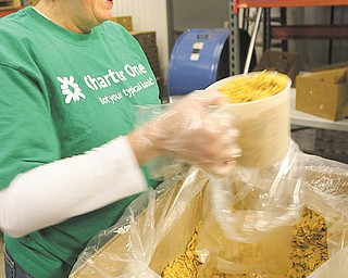 Cup upon cup of bulk cereal is placed in bags by Casey Martin, who was among Charter One Bank employees who volunteered at Second Harvest Food Bank of the Mahoning Valley on Tuesday.