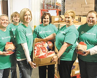Several Charter One volunteers at the food bank warehouse on Salt Springs Road, Youngstown, display some of the 3,012 chickens donated by the Charter One Foundation. From left are Jim Basista, Jenna Howard, Casey Martin, Amy Manolio , Judy Larson, Diana Hogg, Kim Williams and Becky Greenwood. Second Harvest received a $10,000 grant from the Charter One Foundation.