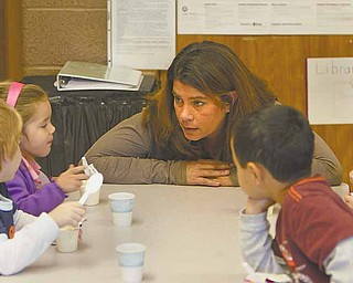 Michelle Frease, director of St. Rose Sunny Days Child Care Center in Girard, talks with students ages 3  to 4 during snack time. Sunny Days has zero state licensing violations, a record Frease attributes to low classroom ratios and a diligent teaching staff.