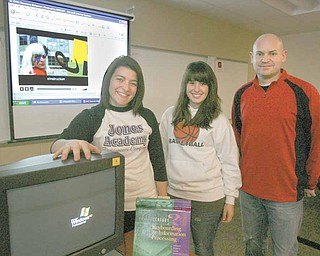 """Alli Fonce (left) and Lisa Holmes, both seniors at Girard High, with their teacher,  Jamie Williams.  stand in front of the story boards that became the video, """"Just Learn,"""" a parody of Lady Gaga's """"Just Dance."""" The video, which was conceived, cast, filmed, edited and produced by GHS digital media students, is one of five finalists in the 2010 eInstruction Classroom Makeover Contest."""