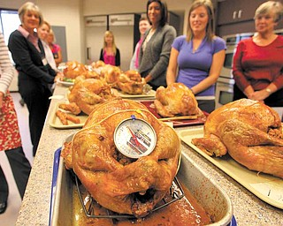 Trainees stand behind their cooked turkeys awaiting critique during training for Butterball talk-line employees on October 20, 2010, in Naperville, Illinois.