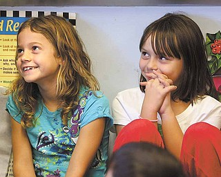 Courtney Mercer and Madison Kish, third-graders at Lloyd Elementary in Austintown, listen intently during Stacey Lundgren's Bucketfilling presentation. At the end of her presentation, Lundgren left a plastic bucket for each classroom.