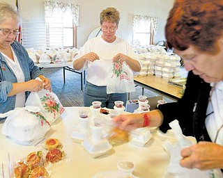 Civil deputies with the Mahoning County Sheriff's Department Senior Services assemble Thanksgiving dinners for seniors Wednesday at First Federated Church of North Jackson. From left are Diane Bates of Youngstown, Michele Nutt of Austintown and Carol Avery of Ellsworth.