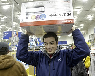 William D. Lewis|The Vindicator A large crowd qued up outside the Boardman Best Buy at 5am Friday to get Black Friday bargins. Nick Mancini of Canfield carries a printer to the check out line.
