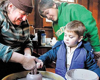 Mary Bobersky, left, of Lake Milton, a vendor at the Olde-Fashioned Christmas at the Mill crafts show, demonstrates how to shape pottery for her nephew, James Auden, 11, also of Lake Milton, and for Jackson Spin, 2, of Boardman.