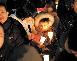 A South Korean child and mom hold candles during a rally against the U.S.-South Korea joint military exercise in Seoul, South Korea, Sunday, Nov. 28, 2010. China tried Sunday to defuse tension over a recent North Korean attack on South Korea by proposing an emergency meeting in Beijing, hours after the U.S. and South Korea launched naval war games in a united show of force.