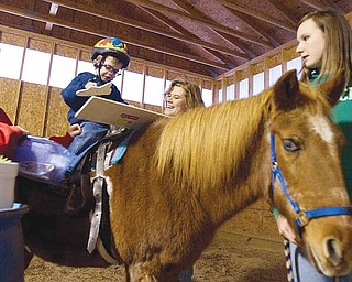 Billy Graff, 3, works to complete a puzzle during a therapeutic riding session at Forget Me Not Horse Farm in Liberty Township. He is assisted by volunteers Rachel Bowser, left, 14, of Liberty, riding instructor Penny Mulichak and Taylor Harshbarger, 14, of Girard.