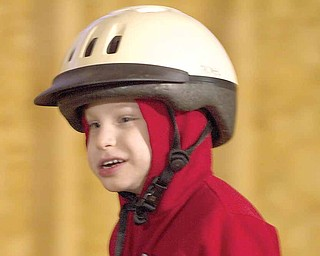 Cody Denmeade, 4, smiles during a therapeutic riding session at the Forget Me Not Horse Farm. Jenessa Spangler, 9, of Cortland, has been fundraising to help Cody attend the sessions, which cost $20 for a half hour.