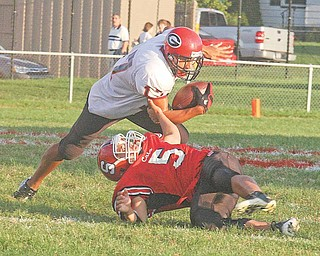 Eric Ahmer (5) makes a one handed tackle of Landon Smith Friday night in Struthers.