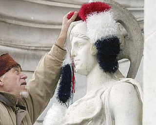 Local artist Ed Hallahan places knitted earmuffs on a sculpture outside the Butler Institute of American Art on Wednesday in preparation for the museum's holiday show this weekend.