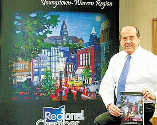 Thomas M. Humphries, President & CEO of the Younstown Warren Regional Chamber, shows a new book promoting the Valley published by the Chamber.