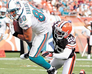 Miami Dolphins tight end Anthony Fasano (80) scores a touchdown as Cleveland Browns cornerback Mike Adams (20) defends in the fourth quarter during an NFL football game in Miami, Sunday, Dec. 5, 2010.