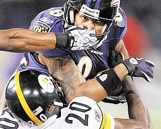 The hand of Pittsburgh Steelers safety Ryan Clark grabs Baltimore Ravens wide receiver T.J. Houshmandzadeh (84) as cornerback Bryant McFadden (20) tackles him during the first half of an NFL football game, Sunday, Dec. 5, 2010, in Baltimore.