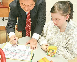 Deng Zhongqing, signs a holiday card that Chelsea Begeot is making in an English class at Girard Junior/Senior High School for overseas service personnel. Deng is in the United States through the Chinene Exchange Initiative, which allows 12 Chinese and 12 American educators to spend two weeks in each other's country. Louise Mason, junior high principal, will go to China in the spring.