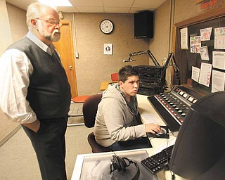 Garrett Hart, a consultant for radio station WAPS in Akron, helps junior Drew Pearson in the WKTL booth next to Tom Krestel's Broadcast Arts classroom at Struthers High School.