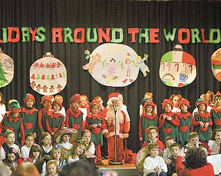 """Santa and his elves marched into the gym at the beginning of the performance of """"Holidays Around the World"""" at Lloyd Elementary School in Austintown. The role of Santa has been played by a first-grader each of the past 30 years."""