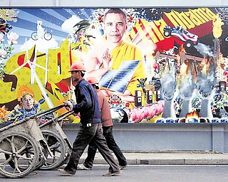 In this photo taken on Thursday Dec. 9, 2010, Chinese workers push carts past a clean energy themed billboard featuring U.S. President Obama as the Buddha on the streets of Shanghai.
