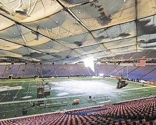 Snow falls into the field from a hole in the collapsed roof of the Metrodome in Minneapolis Sunday, Dec. 12, 2010.  The inflatable roof of the Metrodome collapsed Sunday after a snowstorm that dumped 17 inches (43 cms) on Minneapolis. No one was hurt, but the roof failure sent the NFL scrambling to find a new venue for the Vikings' game against the New York Giants.
