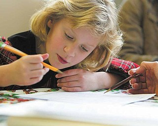 Natalia Novicky, 8, practices use of present tense verbs as part of weekly tutoring. The third-grader is orginally from Ukraine and still learning English at Watson Elementary School.