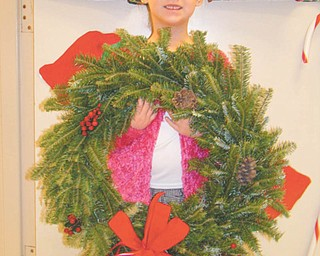Ring in the holidays: Kindergartner Nicolette Leonard displays a live Frasier fir Christmas wreath like the ones St. Patrick School in Hubbard is selling. Each one measures about 22 inches and comes decorated with berries, pinecones and a red ribbon. The cost of each wreath is $28. Wreaths can be purchased at the church, 367 N. Main St., after 4 p.m. Mass on Saturday or after the 9:30 or 11 a.m. Masses on Sunday. If the times are not convenient, call the school at 330-534-2509 to arrange a time. Wreaths can be taken home at the time of purchase.