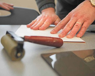 Steven Reese of Youngstown presses his print onto an inked board to create a poinsettia design.