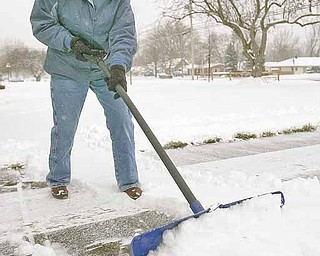 Janet Zolla, of Boardman, shovels snow from her Glenwood Avenue driveway on Tuesday, Dec. 14.