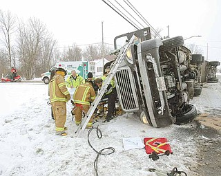 Lane Life Trans paramedics and firefighters from Cardinal Joint Fire District remove the driver from a tractor trailer that overturned Tuesday at the intersection of Leffingwell Road and U.S. Route 62, Canfield.